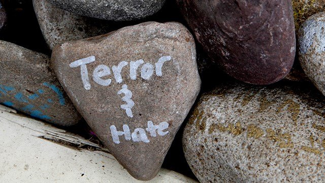 """A rock has the words """"terror and hate"""" written on it at an art installation that encourages the public to write out their fears and leave them behind, along Mt. Vernon Ave in Alexandria, Va. (AP Photo/Jacquelyn Martin)"""