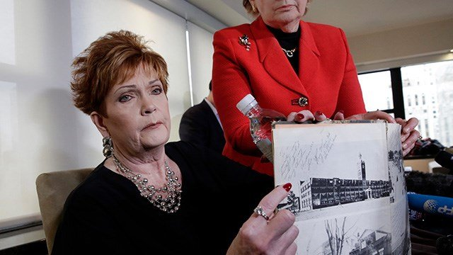 Beverly Young Nelson, left, the latest accuser of Alabama Republican Roy Moore, and attorney Gloria Allred hold Nelson's high school yearbook, signed by Moore, at a news conference. (AP Photo/Richard Drew)