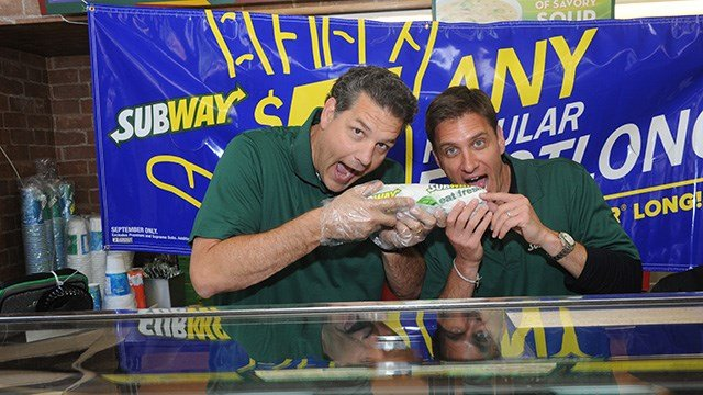Famous Fans Mike Golic, left, and Mike Greenberg, of ESPN, pose behind the counter at a SUBWAY restaurant in New York, Thursday, Sept. 5, 2013. (Photo by Diane Bondareff/Invision for Subway Restaurants/AP Images)