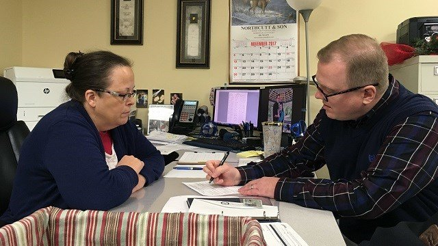 (AP Photo/Adam Beam) David Ermold, right, files to run for Rowan County Clerk in Kentucky as Clerk Kim Davis look on Wednesday, Dec. 6, 2017, in Morehead, Ky. Davis denied Ermold and his husband a marriage license two years ago because she was opposed...