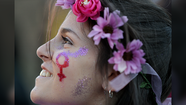 A woman smiles during a demonstration demanding equal rights for women and men, on the occasion of the Women's Day, in Rome, Wednesday, March 8, 2017. (AP Photo/Andrew Medichini)