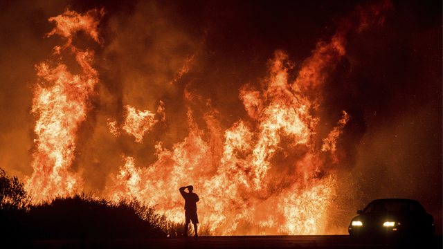 A motorists on Highway 101 watches flames from the Thomas fire leap above the roadway north of Ventura, Calif., on Wednesday, Dec. 6, 2017. (AP Photo/Noah Berger)