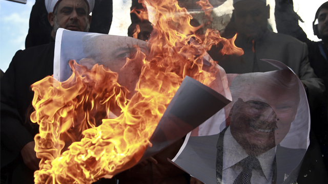 Palestinians burn posters of Israeli Prime Minister Benjamin Netanyahu and U.S. President Donald Trump, during a protest against the U.S. decision to recognize Jerusalem as Israel's capital, in Gaza City Thursday, Dec. 7, 2017. (AP Photo/ Khalil Hamra)