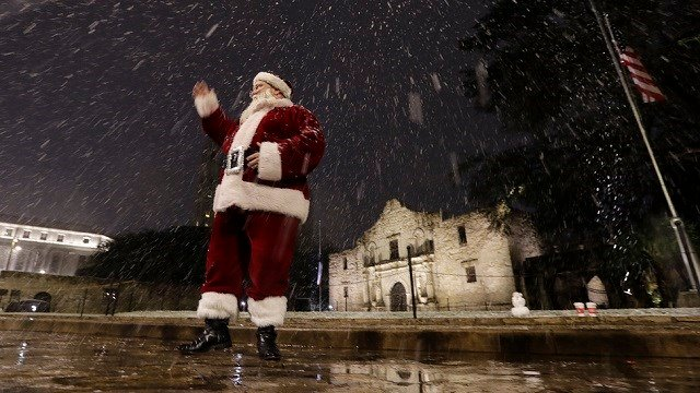 (AP Photo/Eric Gay) Dressed as Santa Claus, Eldon Hansen stands in front of the Alamo as snow falls in downtown San Antonio, Thursday, Dec. 7, 2017. The National Weather Service said up to 2.5 inches of snow had been measured in the San Antonio area.