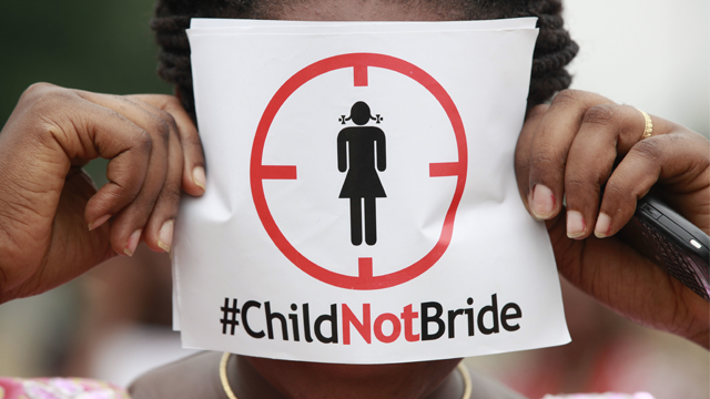 a woman protests against underage marriage in Lagos, Nigeria. Child marriage affects nearly 15 million girls around the world, and West and Central Africa has six of the 10 countries with the highest rate. (AP Photo/Sunday Alamba, File)