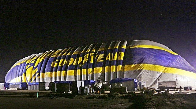(Goodyear Tire & Rubber Co. via AP)  The building standing nine stories tall and stretching the length of a football field went up early Wednesday along Interstate 405 south of Los Angeles.