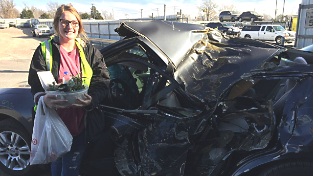 Julia Jolly stands next to her totaled car. (Credit: KFOR via CNN)