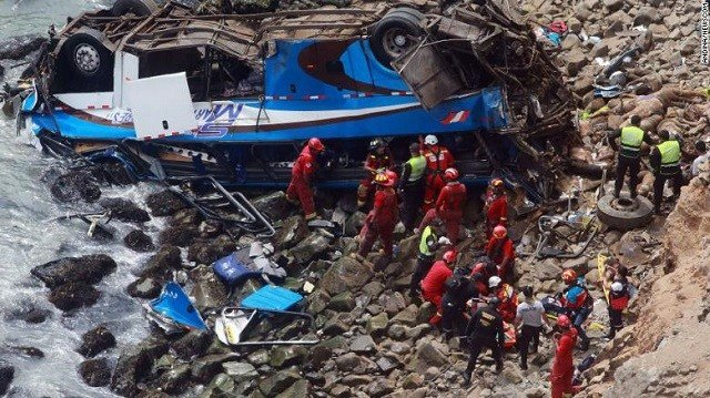 (Vidal Tarky, Andina News Agency via AP) In this photo provided by the government news agency Andina, firemen recover bodies from a bus that fell off a cliff after it was hit by a tractor-trailer rig, in Pasamayo, Peru, Tuesday, Jan 2, 2018.