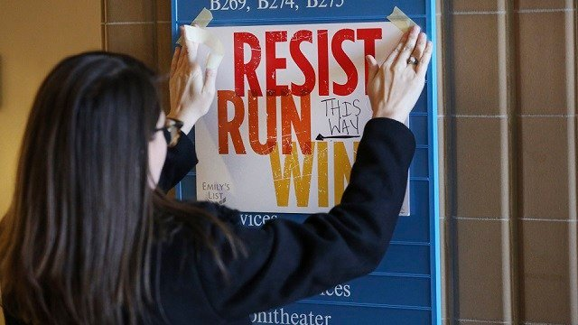 (AP Photo/LM Otero) In this Saturday, Dec. 9, 2017 photo, Lianna Stroster posts a sign directing to a women's candidate training workshop at El Centro College in Dallas.