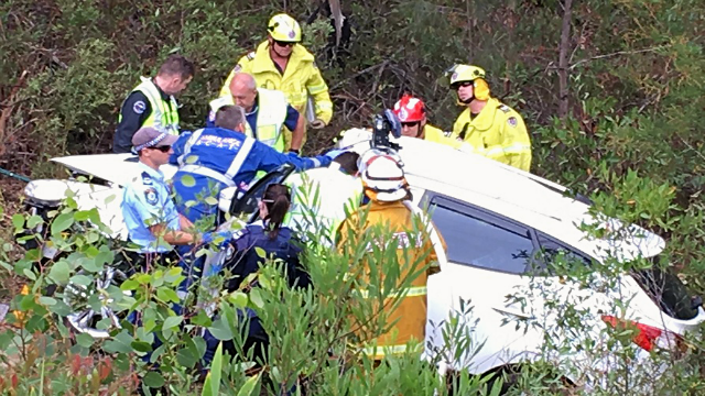 This Monday, Jan. 15, 2018, photo taken and provided by Michael Lethbridge, emergency services officers work to cut his nephew Samuel Lethbridge, 17, from the wreck of his car off the Pacific Highway south of Swansea in New South Wales state, Australia.