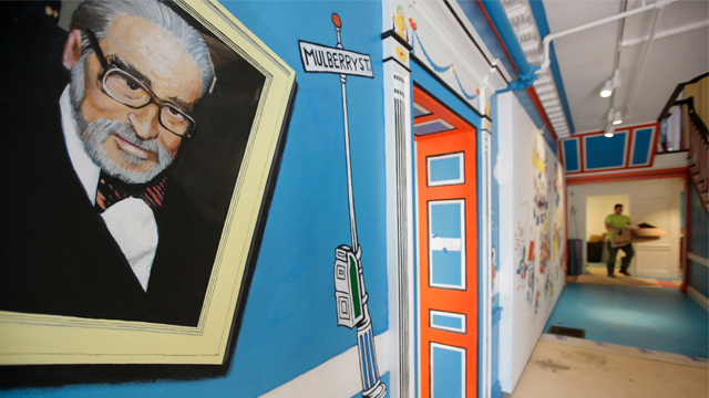 In this May 4, 2017, photo a mural that features Theodor Seuss Geisel, left, also know by his pen name Dr. Seuss, rests on a wall near an entrance at The Amazing World of Dr. Seuss Museum. (AP Photo/Steven Senne)
