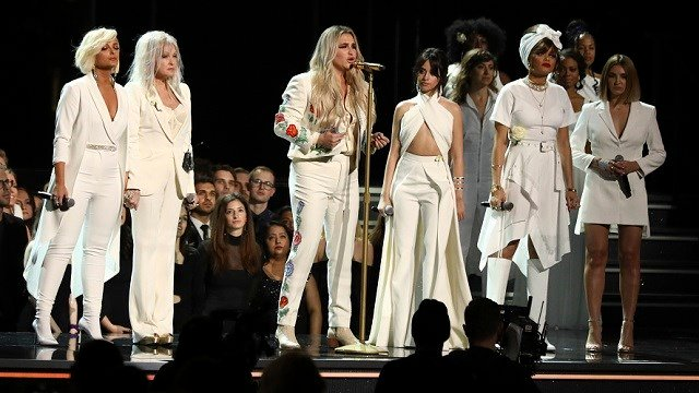 "Kesha, center, performs ""Praying"" as, from left, Bebe Rexha, Cyndi Lauper, Camila Cabello, Andra Day and Julia Michaels look on at the 60th annual Grammy Awards at Madison Square Garden on Sunday, Jan. 28, 2018, in New York. (Photo by Matt Sayles/Invision"
