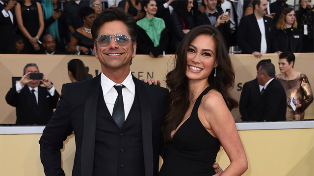 In this Jan. 21, 2018 file photo, John Stamos, left, and Caitlin McHugh arrive at the 24th annual Screen Actors Guild Awards at the Shrine Auditorium & Expo Hall in Los Angeles. (Photo by Jordan Strauss/Invision/AP, File)