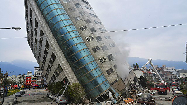 A residential building leans on a collapsed first floor following an earthquake, Wednesday, Feb. 7, 2018, in Hualien, southern Taiwan. (Central News Agency via AP)