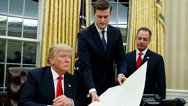 (AP Photo/Evan Vucci) In this Jan. 20, 2017 file photo, White House Staff Secretary Rob Porter, center, hands President Donald Trump a confirmation order for James Mattis as defense secretary, in the Oval Office of the White House in Washington, as...