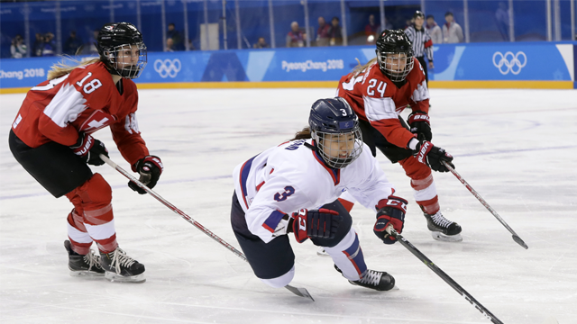 South Korea's Eom Suyeon, of the combined Koreas team, chases the puck against Tess Allemann (18) and Isabel Waidacher (24), of Switzerland, during the first period.  (AP Photo/Frank Franklin II)