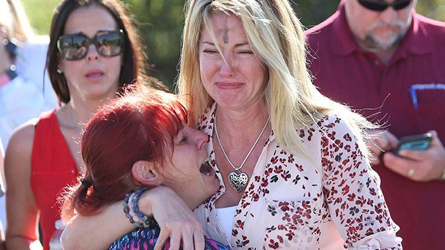 Parents wait for news after a reports of a shooting at Marjory Stoneman Douglas High School in Parkland Fla. on Wednesday Feb. 14 2018