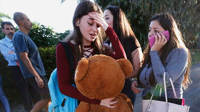 (AP Photo/Wilfredo Lee) Students wait to be picked up after a shooting at Marjory Stoneman Douglas High School in Parkland, Fla., Wednesday, Feb. 14, 2018.