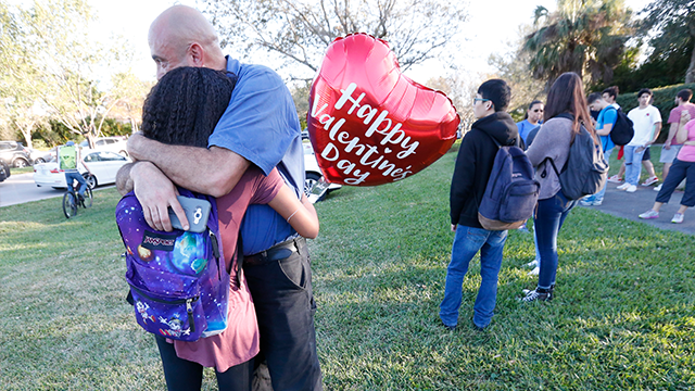 Family members embrace following a shooting at Marjory Stoneman Douglas High School, Wednesday, Feb. 14, 2018, in Parkland, Fla. (AP Photo/Wilfredo Lee)