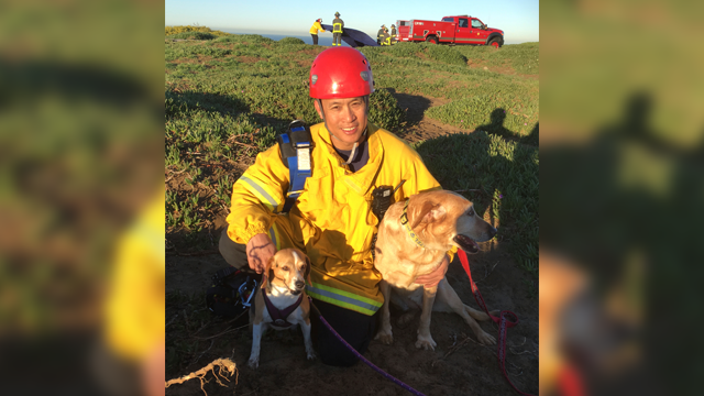 In this photo provided by the San Francisco Fire Department, firefighter and paramedic Art Julaton poses with a pair of dog's that he helped rescue from a cliff, Friday, Feb. 16, 2018, in San Francisco. (San Francisco Fire Department via AP)