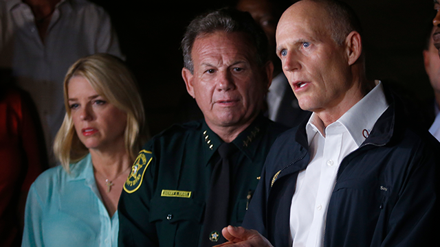 (AP Photo/Wilfredo Lee) Florida Gov. Rick Scott, foreground, speaks along with Sheriff Scott Israel, center, of Broward County, and Pam Bondi, Florida Attorney General, during a news conference near Marjory Stoneman Douglas High School in Parkland, Fla.
