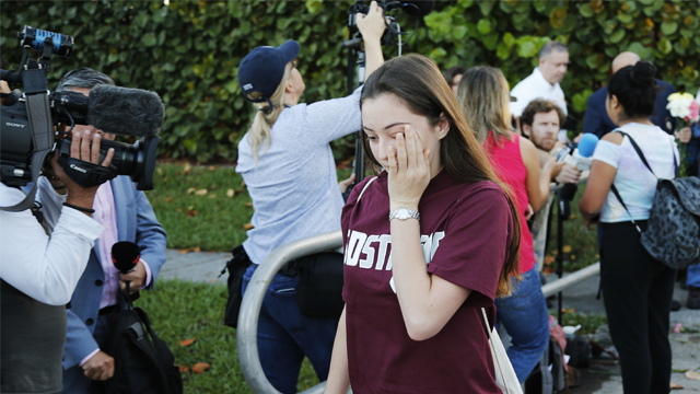 A student walks past the media at Marjory Stoneman Douglas High School in Parkland, Fla., Wednesday, Feb. 28, 2018. Students returned to class for the first time since a former student opened fire there with an assault weapon. (AP Photo/Terry Renna)