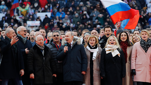 (AP Photo/Pavel Golovkin) Russian President Vladimir Putin, center, and other guests sing Russian national anthem during a massive rally in his support as a presidential candidate at the Luzhniki stadium in Moscow, Russia, Saturday, March 3, 2018.