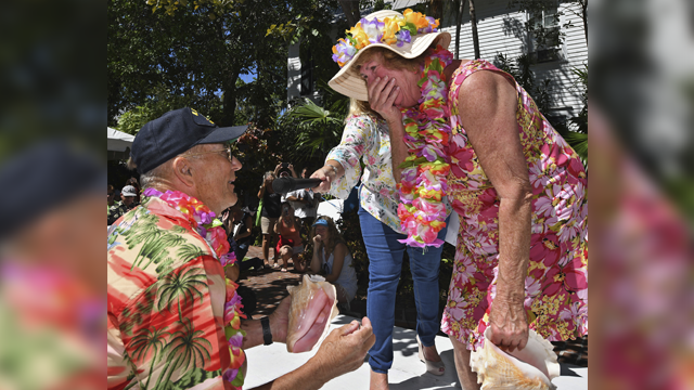 In this photo provided by the Florida Keys News Bureau, Mary Lou Smith, right, reacts to a surprise marriage proposal from Rick Race after she competed in the Conch Shell Blowing Contest. (Rob O'Neal/Florida Keys News Bureau via AP)