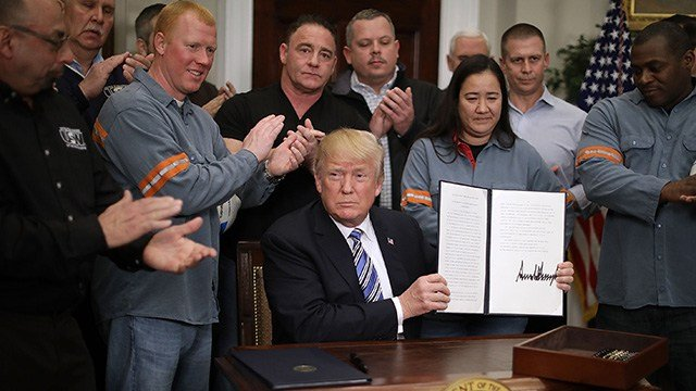 Surrounded by applauding steel and aluminum workers, U.S. President Donald Trump holds up the 'Section 232 Proclamations' on steel imports that he signed in the Roosevelt Room of the White House March 8, 2018. (Photo by Chip Somodevilla/Getty Images)