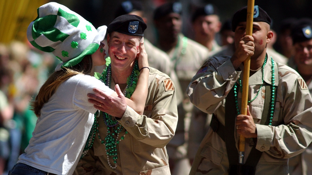Col. Ronald Tuggle is kissed Friday, March 17, 2006, while marching with his unit of the Army's 3rd Infantry Division in Savannah, Ga., during the annual St. Patrick's Day parade. (AP Photo/Stephen Morton)