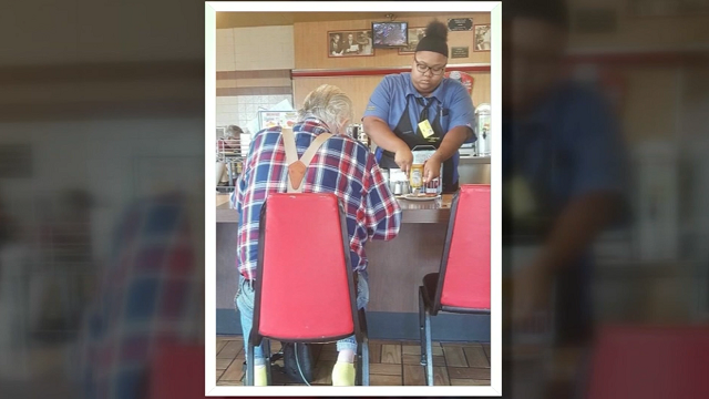 In this photo provided by Laura Wolf, 18-year-old Evoni Williams helps a Waffle House patron cut up is food. (Source: Laura Wolf via KHOU, CNN)