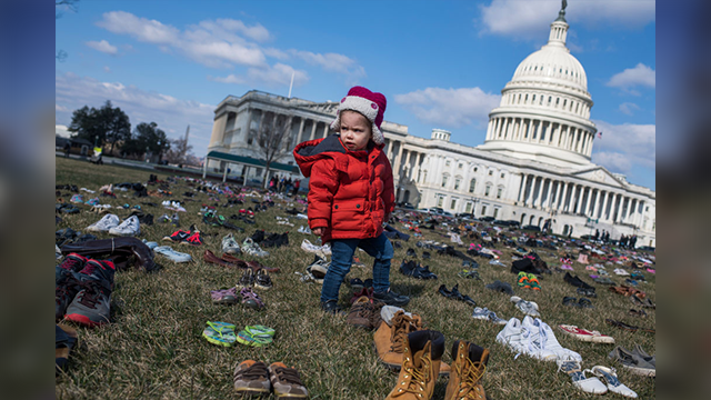 (Photo By Tom Williams/CQ Roll Call) Evelyn Black, 2 1/2, of Capitol Hill, walks through about 7000 pairs of shoes that are displayed on the east lawn of the Capitol on March 13, 2018, to represent the 7000 children who were killed by guns since...