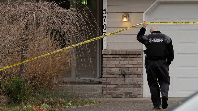 A Pierce County Sheriff's Dept. deputy walks under crime scene tape, Tuesday, March 13, 2018, in front of a home in Spanaway, Wash. (AP Photo/Ted S. Warren)