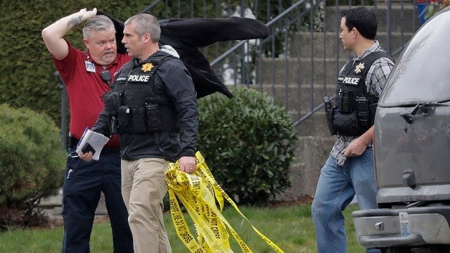 Officials carry crime scene tape, Tuesday, March 13, 2018, as they leave a home in Spanaway, Wash. (AP Photo/Ted S. Warren)