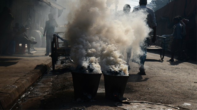 """Indian commuters walk past as dense smoke pours out of """"chulahs"""" -- traditional coal ovens -- placed on the side of a busy road in Kolkata in February, 2018. (AFP/Getty Images)"""