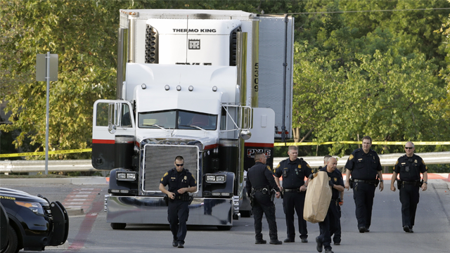 San Antonio police officers investigate the scene where eight people were found dead in a tractor-trailer loaded with at least 30 others outside a Walmart store. (AP Photo/Eric Gay)