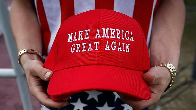"In this Dec. 17, 2016 file image, a man dressed in American flag clothes holds ""Make America Great Again"" hats. (AP Photo/Brynn Anderson)"