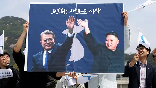 South Koreans hold up placards during a rally welcoming the planned Inter Korean Summit in front of Presidential Blue House on April 26. (CNN)