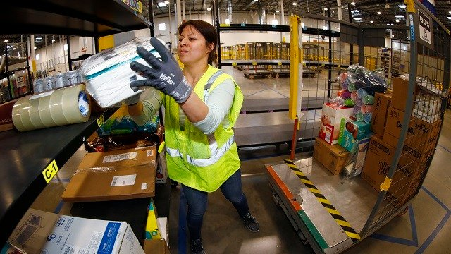 A worker moves an item from a cart to the line for boxing during a tour of the Amazon fulfillment center Thursday
