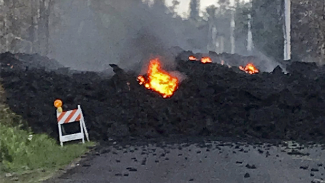 This photo provided by Hawaii Electric Light shows lava flowing over Mohala Street in the Leilani Estates area near Pahoa on the Big Island of Hawaii Friday, May 4, 2018. (Hawaii Electric Light via AP)