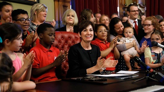 Iowa Gov. Kim Reynolds, center, cheers after signing a six-week abortion ban bill into law during a ceremony in her formal office May 4, 2018. The bill gives Iowa the strictest abortion restrictions in the nation. (AP Photo/Charlie Neibergall)