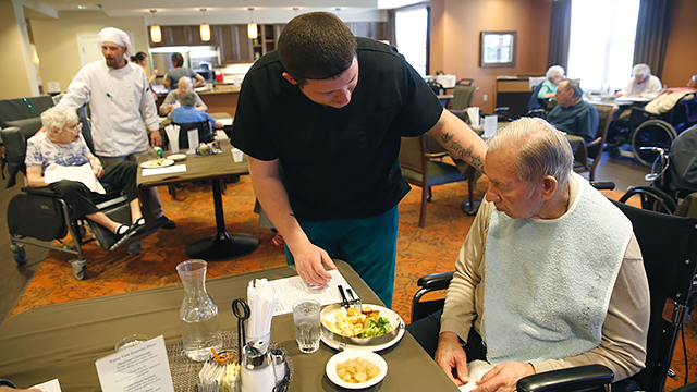In this file photo, a certified nursing assistant brings meals to residents.(AP Photo/Brennan Linsley)