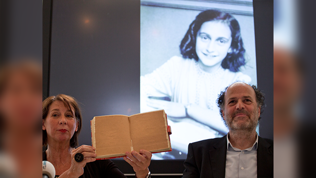 Teresien da Silva, left, and Ronald Leopold of the Anne Frank Foundation show a facsimile of Anne Frank's diary with two pages taped off during a press conference at the foundation's office in Amsterdam, Netherlands, Tuesday, May 15, 2018. (AP Photo)