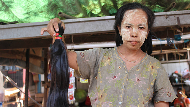 Aye Aye Thein, 55, cuts hair for a living at Insein market in the north of Yangon, Myanmar's largest city. (Libby Hogan/CNN)