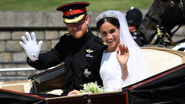 Britain's Prince Harry, Duke of Sussex and his wife Meghan, Duchess of Sussex wave from their carriage on Castle Hill outside Windsor Castle in Windsor, England after their wedding ceremony Saturday, May 19, 2018. (Paul Ellis/pool photo via AP)