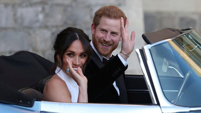 The Duke and Duchess of Sussex, Meghan Markle and Prince Harry, leave Windsor Castle in a convertible car after their wedding to attend an evening reception at Frogmore House, hosted by the Prince of Wales, May 19, 2018. (Steve Parsons/pool photo via AP)