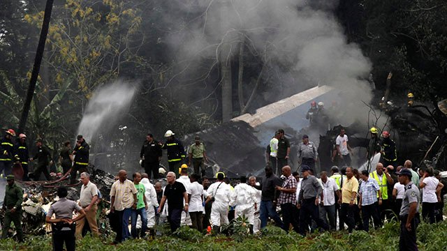 Cuba's President Miguel Diaz-Canel, third from left, walks away from the site where a Boeing 737 plummeted into a yuca field with more than 100 passengers on board. (AP Photo/Enrique de la Osa)