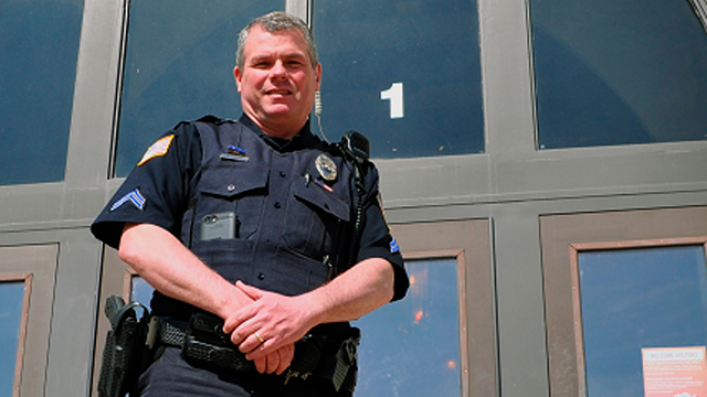In this undated photo provided by City of Dixon, police officer Mark Dallas poses for a photo in front of Dixon High School in Dixon, Ill. (City of Dixon via AP)