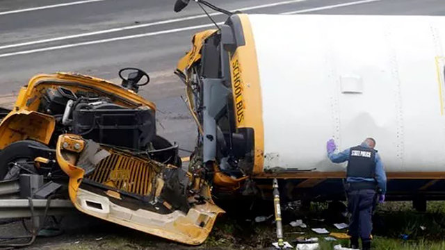 A state police officer works at the scene of a school bus and dump truck collision, injuring multiple people, on Interstate 80 in Mount Olive, N.J., Thursday, May 17, 2018. (AP Photo/Seth Wenig)