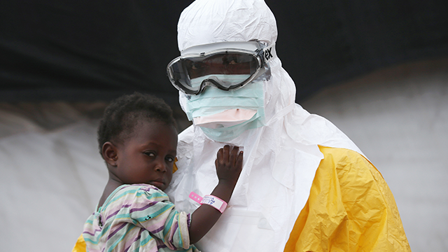 A Doctors Without Borders (MSF), health worker in protective clothing holds a child suspected of having Ebola in the MSF treatment center on October 5, 2014 in Paynesville, Liberia. (Photo by John Moore/Getty Images)